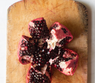 a segmented pomegranate sitting on a wooden cutting board