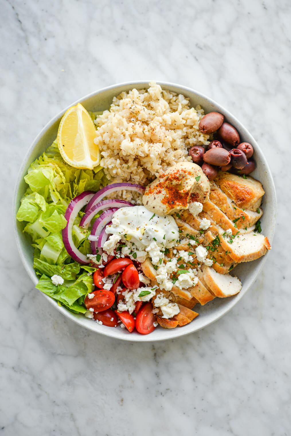 a green chicken power bowl made with brown rice, chicken, olives, cherry tomatoes, hummus, and lettuce