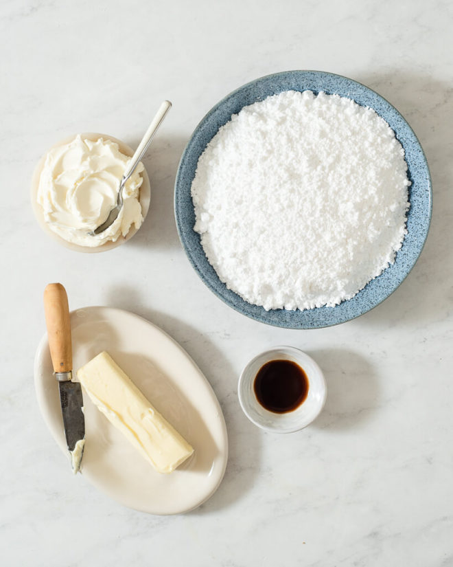 all of the ingredients for classic cream cheese frosting in different sized bowls on a marble surface