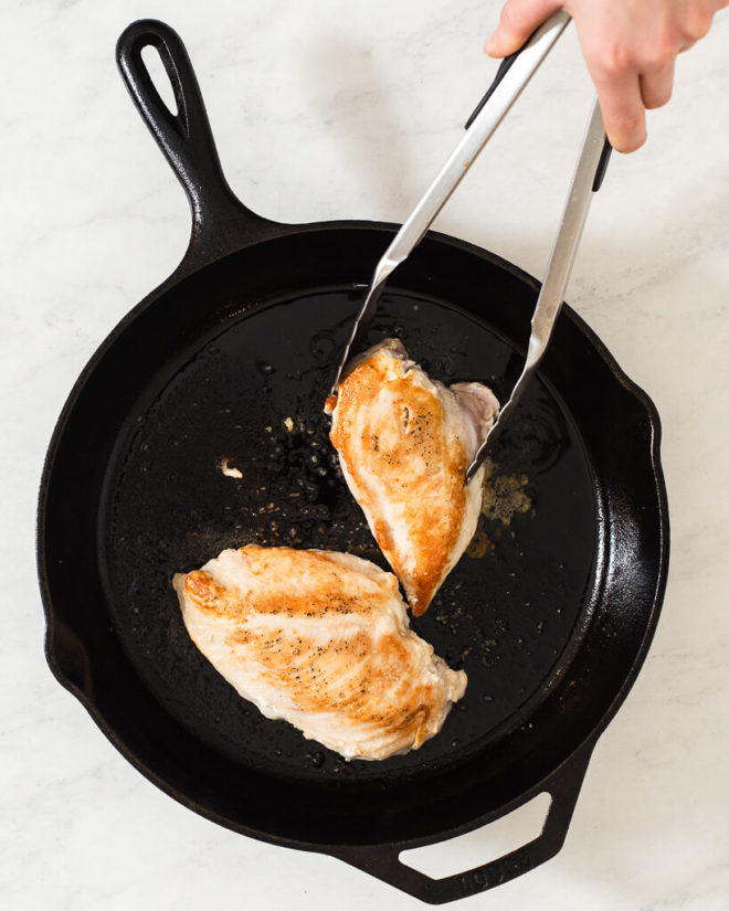 a person searing chicken breasts in a cast iron skillet