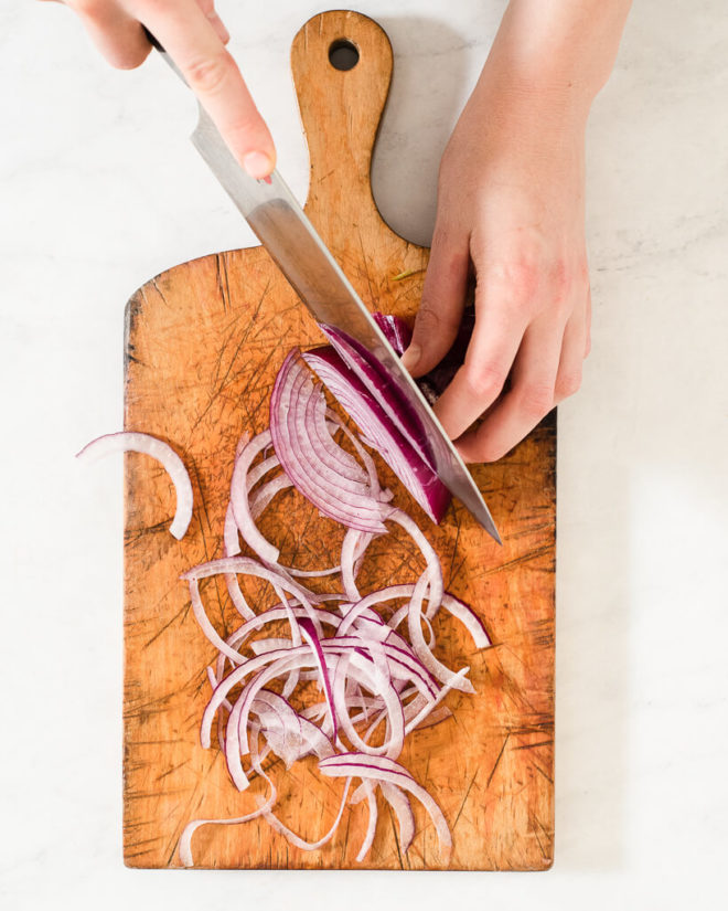 a person slicing purple onions on a cutting board