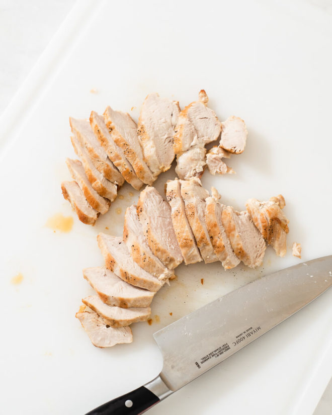 sliced chicken on a cutting board next to a knife