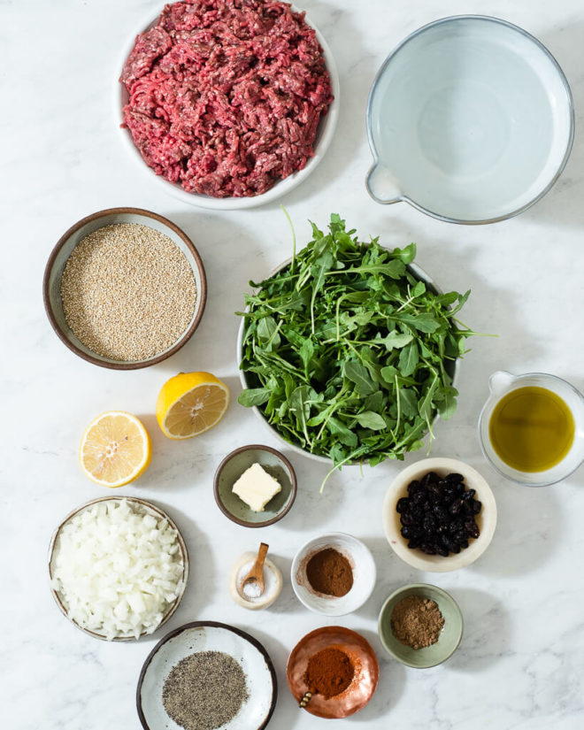 all of the ingredients for a greek style meatball dinner in different sized bowls and plates on a marble surface