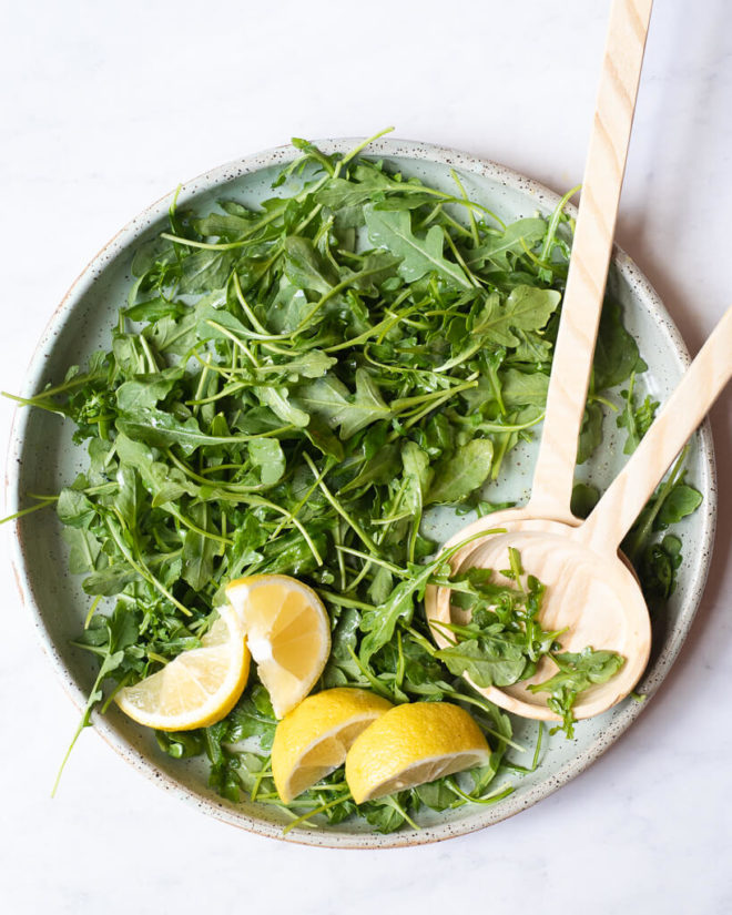 a simple arugula salad on a plate with lemon wedges and wooden serving spoons