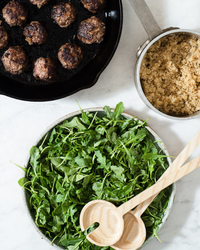 a cast iron skillet of greek meatballs, a pot of white quinoa, and a bowl of simple arugula salad on a marble surface