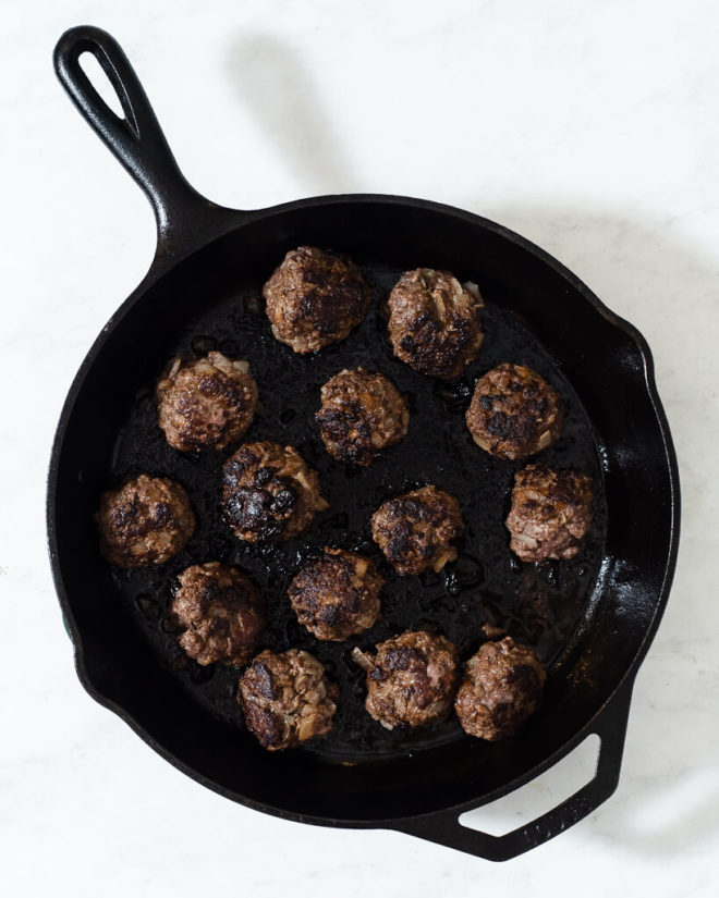 a cast iron skillet with greek style meatballs searing in it