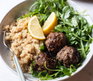 a serving of greek meatballs, arugula salad, and white quinoa served with 2 lemon wedges