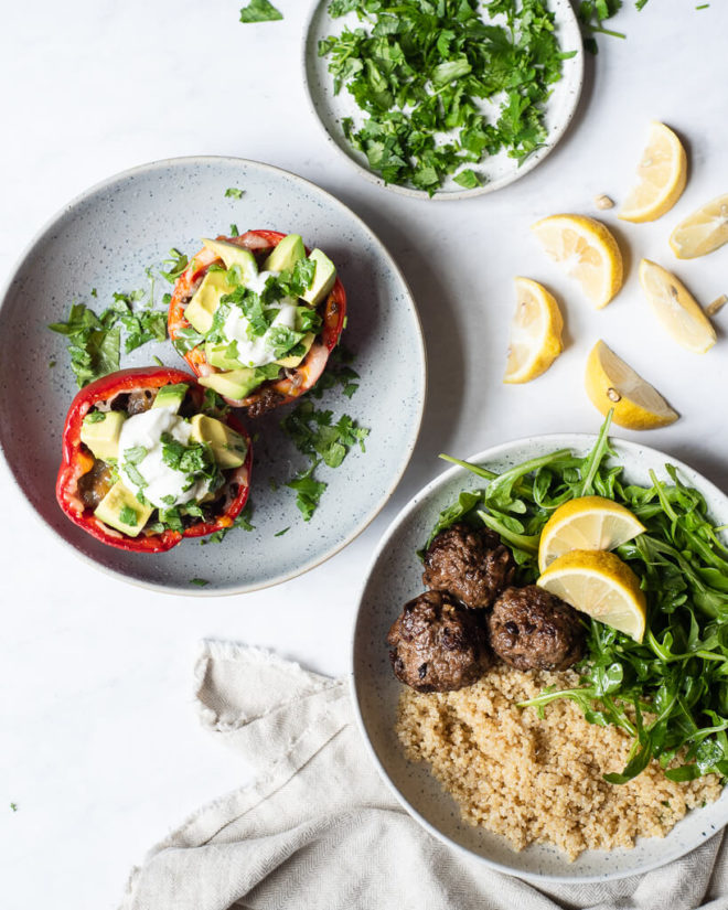 a serving of tex mex stuffed peppers and greek meatballs on plates
