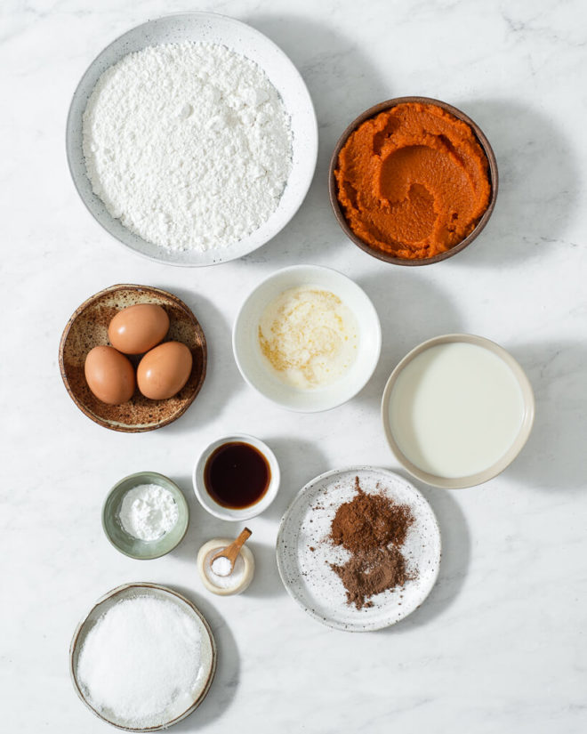 the ingredients for pumpkin pancakes in small bowls and plates on a marble surface