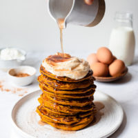 a stack of pumpkin pancakes topped with whipped cream, cinnamon, and maple syrup