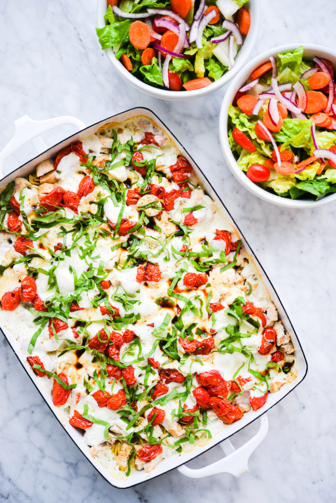 a caprese chicken casserole next to two bowls of Italian side salad