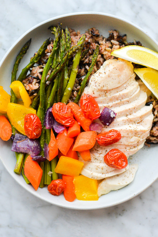 a plate of roasted chicken breast, roasted veggies, and wild rice served with two lemon wedges