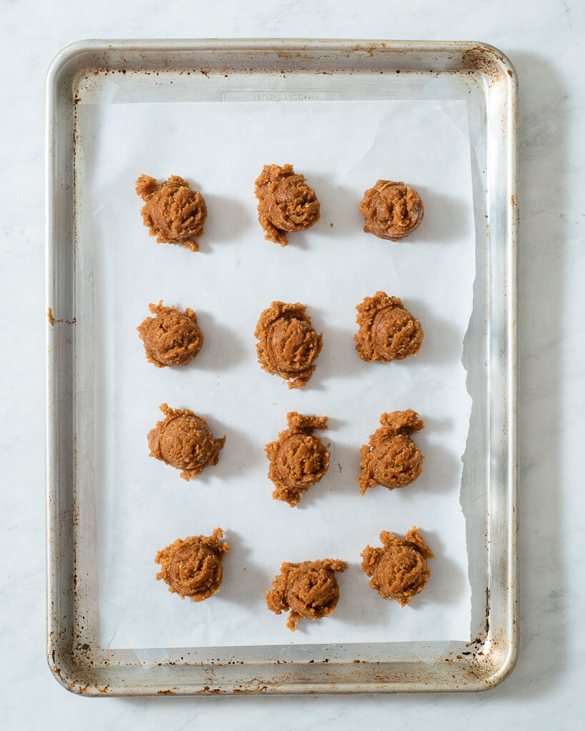 keto peanut butter cookie dough balls on a parchment paper lined baking sheet