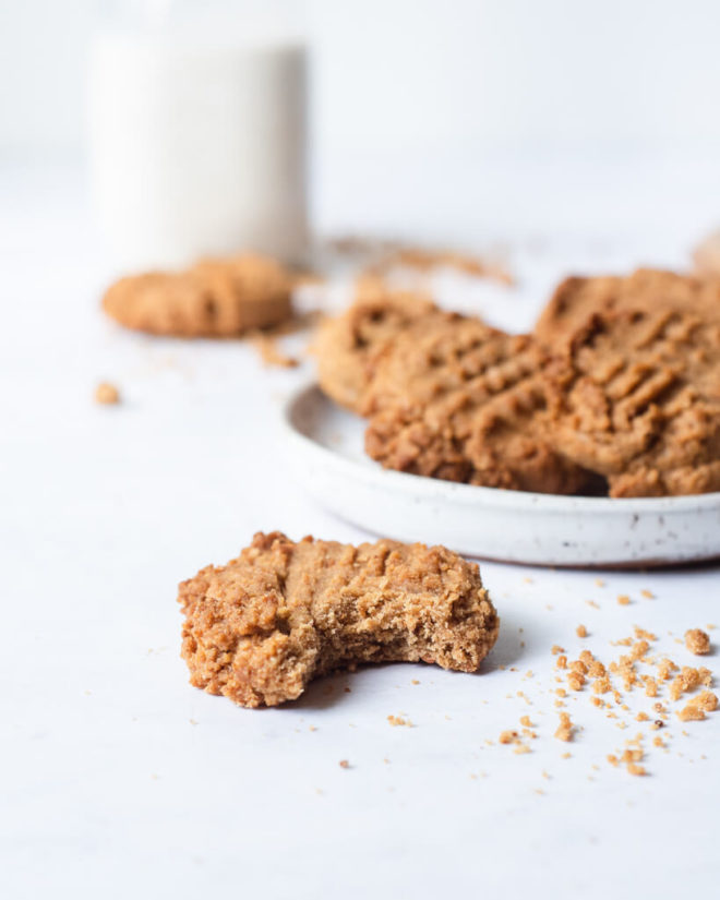 a keto peanut butter cookie with a bite taken out in front of a plate of keto peanut butter cookies