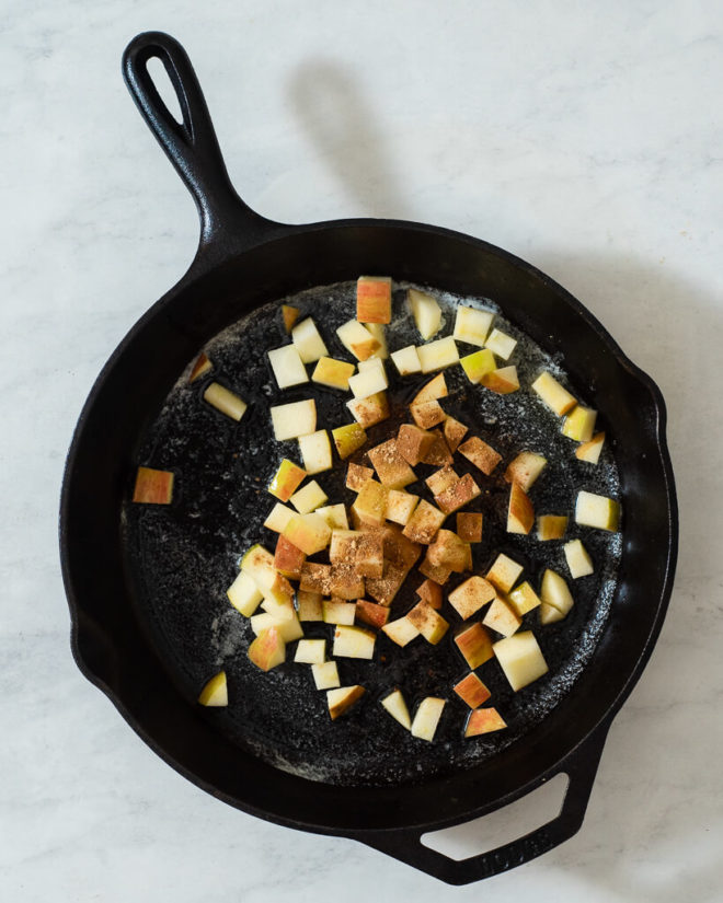 a cast iron skillet with cubed cinnamon apples