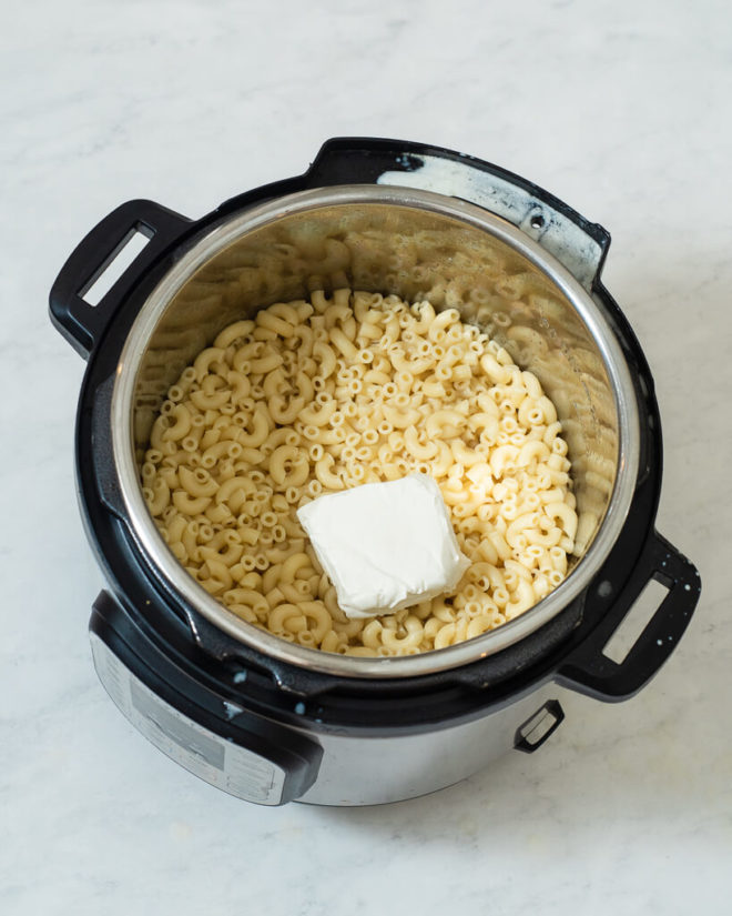cooked macaroni noodles in an instant pot with a block of cream cheese sitting on top