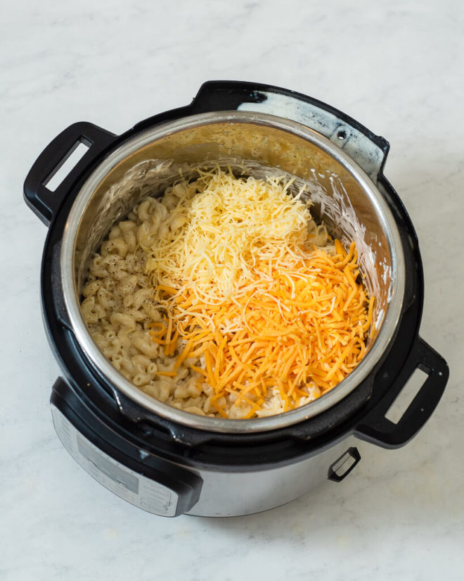 an instant pot with cooked macaroni in it and shredded cheese on top