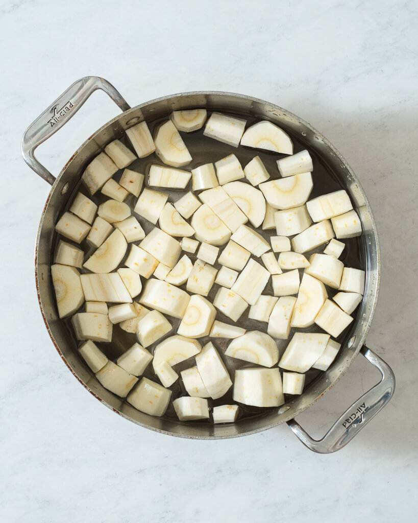chopped parsnips in a stainless pot filled with water