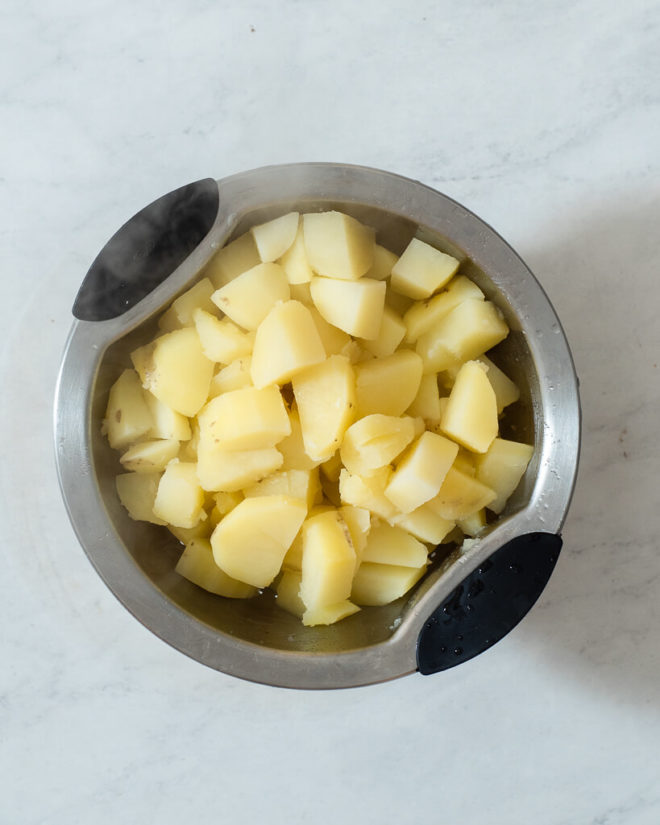 a bowl of softened chunks of potatoes