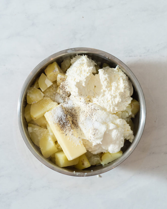 all of the ingredients for creamy mashed potatoes in a mixing bowl before being whipped together