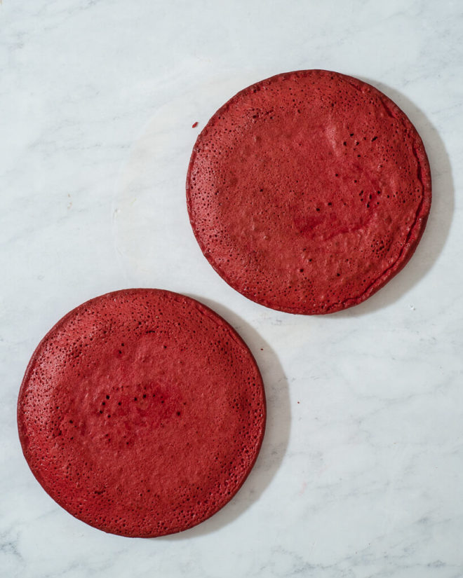 two round red velvet cakes on a marble surface