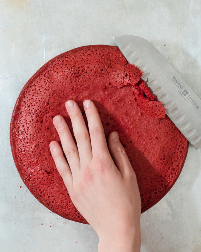 a person slicing the rounded off part of a circular red velvet cake