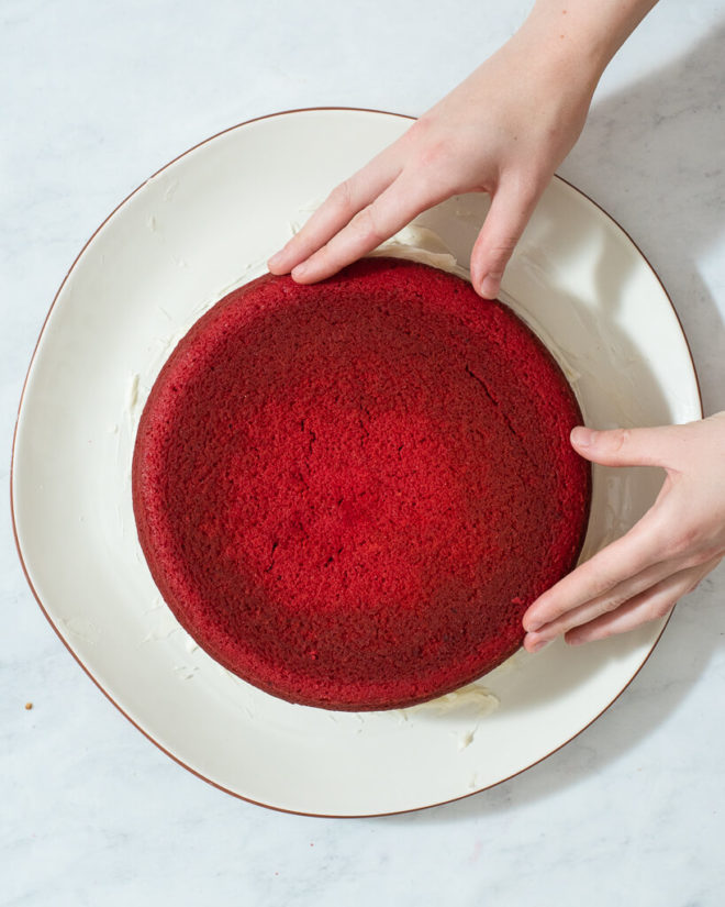 a person stacking two round red velvet cakes on top of each other