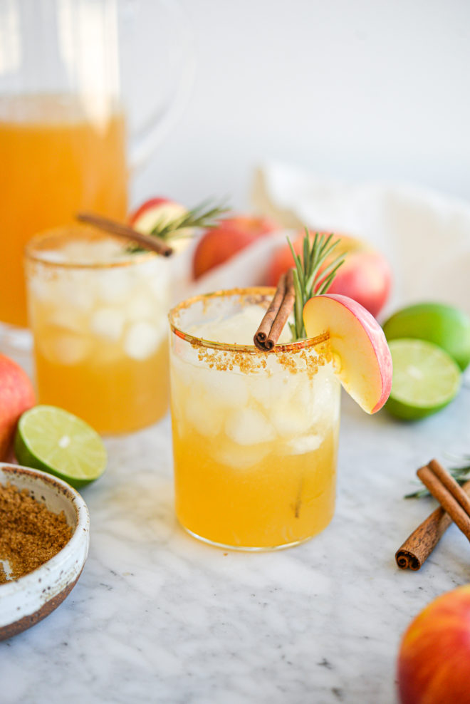 two apple cider margaritas next to a pitcher of margaritas next to apples, limes, brown sugar, cinnamon sticks, and rosemary