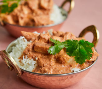 a copper bowl of Indian-inspired butter chicken over white rice