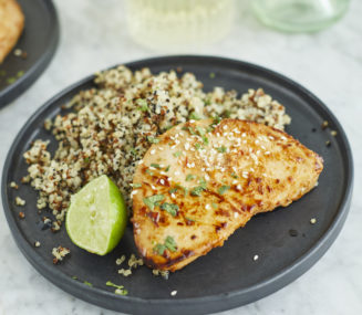 a chili lime tuna steak next to quinoa and a wedge of lime on a plate