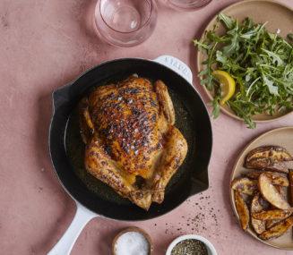 roasted chicken next to arugula salad and roasted potato wedges