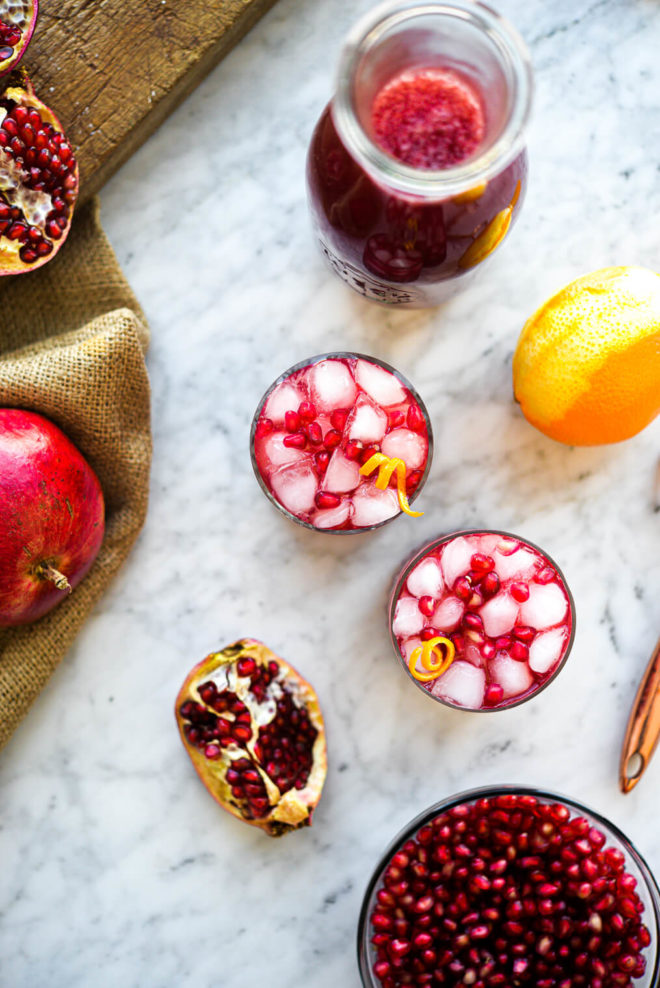 two pomegranate margaritas sitting in front of a bowl of pomegranate arils and whole pomegranates
