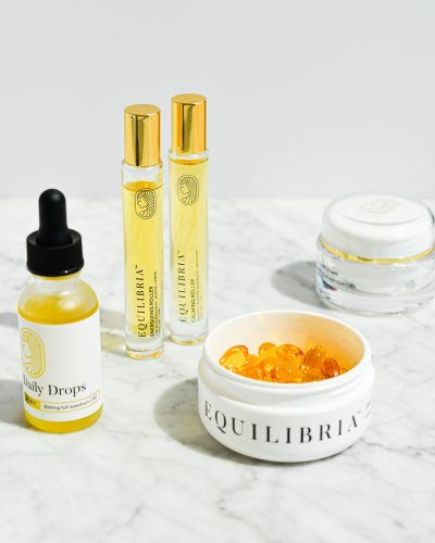 equilibria cbd drops, roller, softgels, and cbd cream on a marble surface