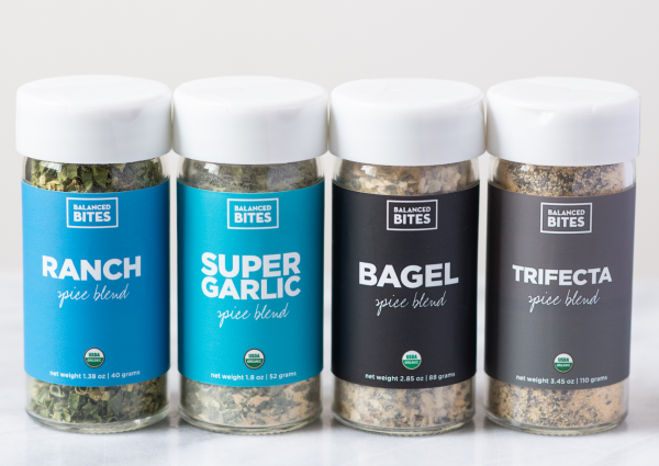 4 jars of balanced bites spices lined up in a row on a marble surface